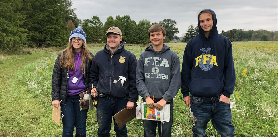 4 STUDENTS STANDING IN A FIELD WITH CLIPBOARDS FROM THE SOIL JUDGING CONTEST THAT THEY PLACE 7TH IN THE STATE COMPETITION.