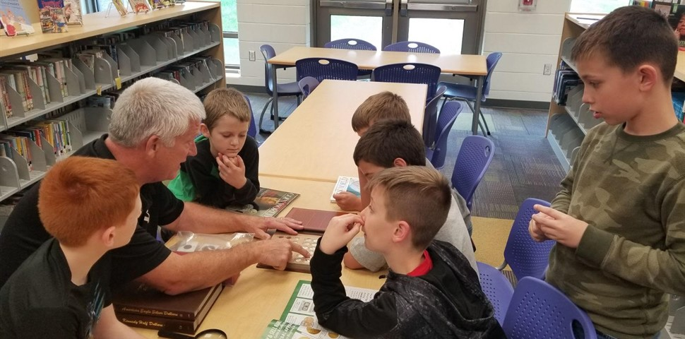 Principal Powell with 6 students teaching art of coin collecting around a table.