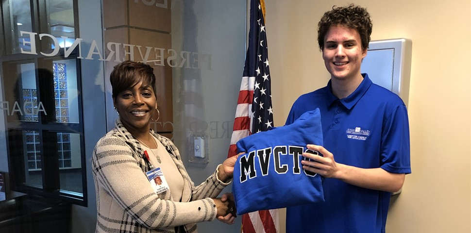 Alex Newport standing with Principal Norvell receiving a blue sweatshirt with black lettering.