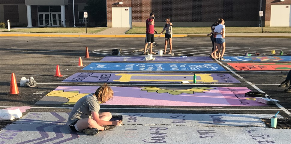 MULTIPLE STUDENTS WORKING ON PAINTING THEIR HS PARKING SPOTS