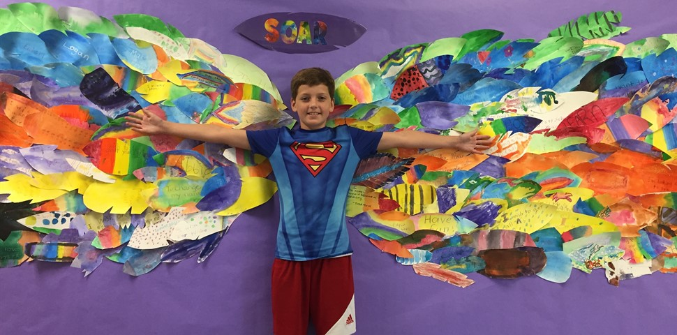 student standing in front of eagle wing art project