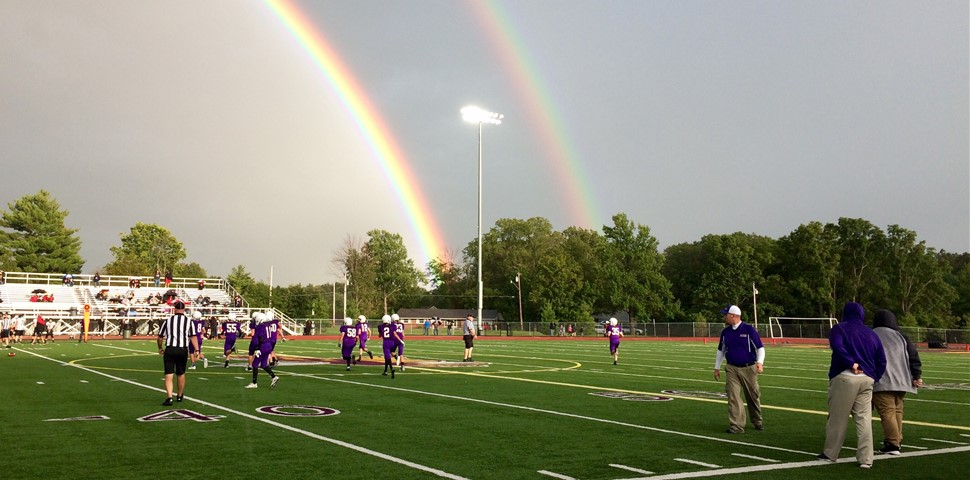 Middle School Football  team playing with rainbow in the background.