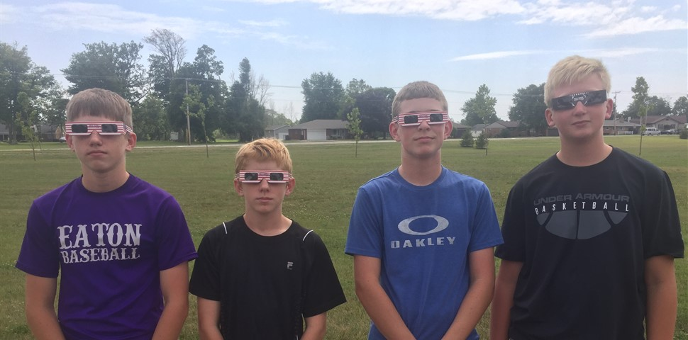 Four students standing with solar eclipse glasses