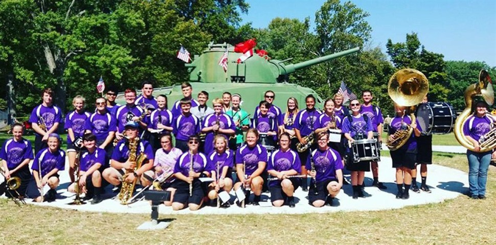 Middle school band sitting in front of Miss Preble military tank